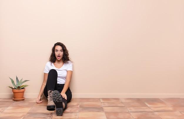 Молодая женщина выглядит очень шокированной или удивленной, смотрит с открытым ртом и говорит: «вау», сидя на полу террасы