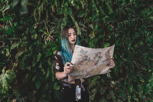 Young woman looking at vintage map standing in front of plant