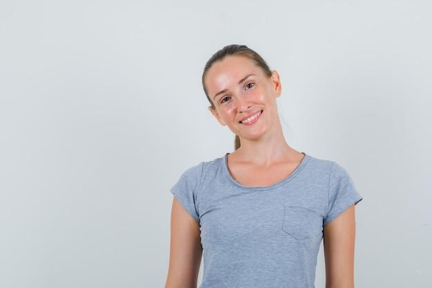 灰色のtシャツの正面図で笑顔で見ている若い女性。