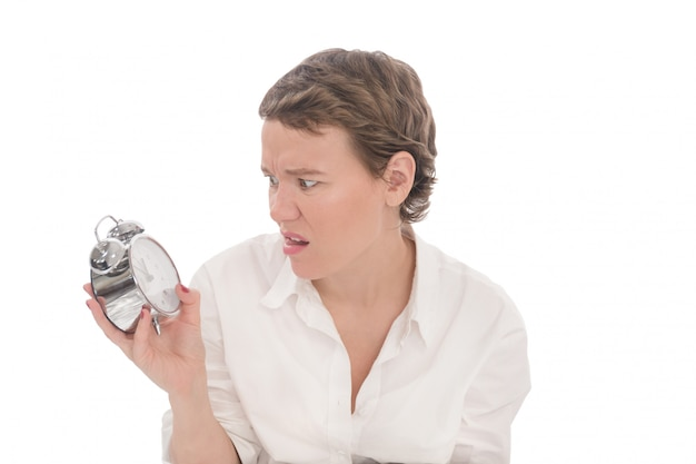Young woman looks at alarm clock displeased