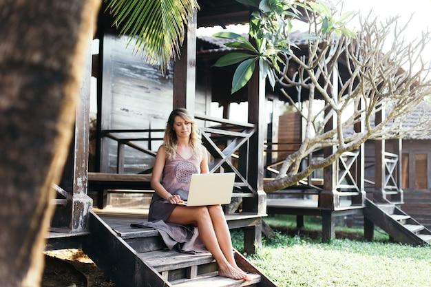 젊은 여자는 그녀의 방갈로의 현관에 앉아있는 동안 그녀의 노트북을 살펴 봅니다. 관광 및 레크리에이션. 현대 기술. 여행 및 무선 통신. 자연과 평온. 젊음과 아름다움.