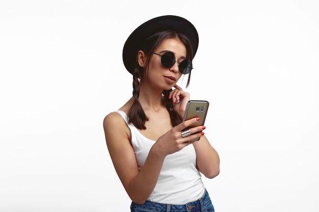 Молодая женщина смотрит на экран смартфона, наслаждается онлайн-чатом над белой стеной