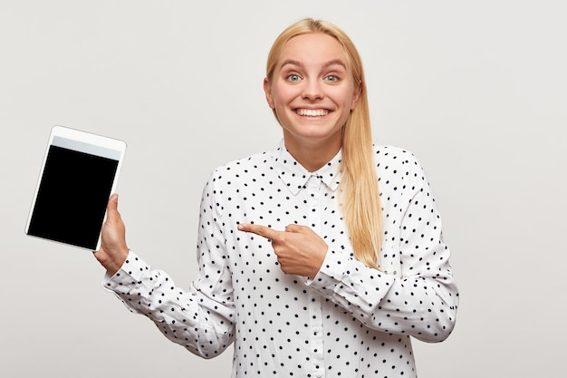 Young woman looks delighted gladden amazed happily toothy smiles, tablet in hand pointing with finger on it