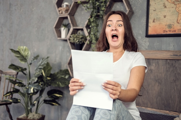 Young woman looks at the documents in surprise