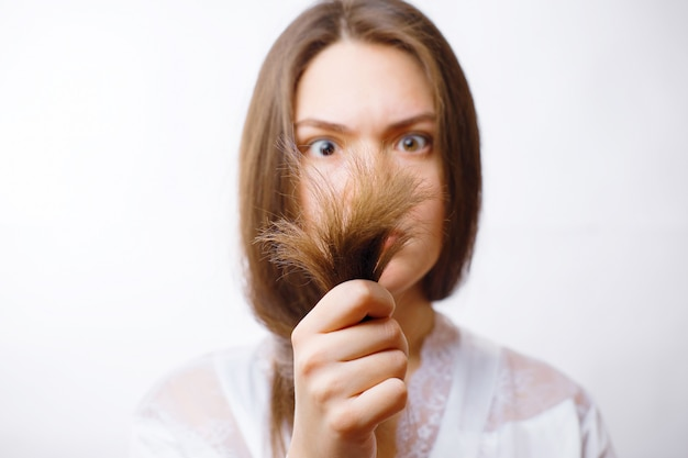 Young woman looks at her spoiled split ends of hair