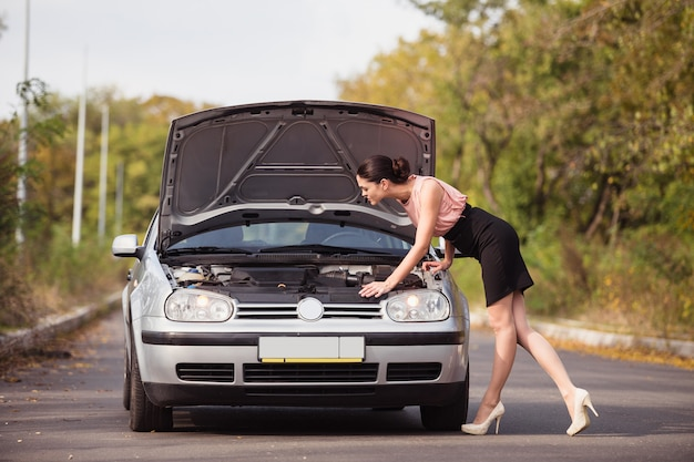 Young woman looks under the hood of her car and trying to find the cause of breakage