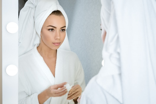 A young woman looks in the mirror with a towel on her head, holding a face cream. skin care concept at hom