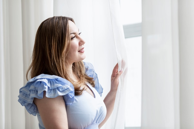 A young woman looks tenderly out the window. plus size brunette. it's a lovely morning. close-up.