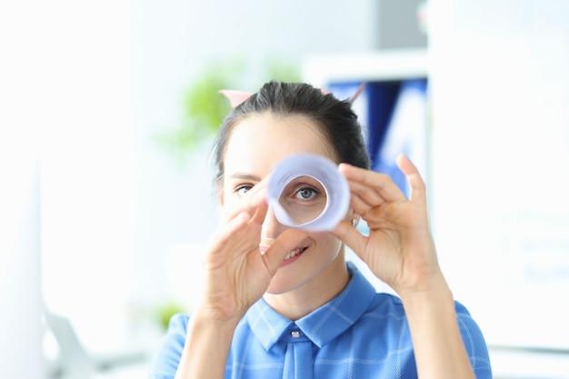 젊은 여성은 종이로 만든 쌍안경을 통해 새로운 비즈니스 솔루션 개념을 찾습니다