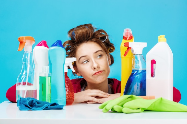 Young woman looks tired sitting behind table with cleaning tools