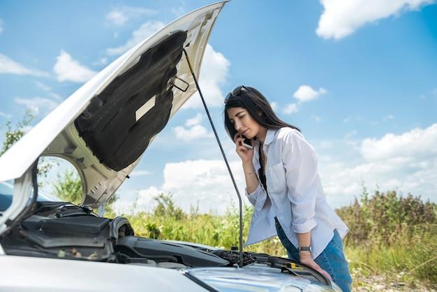 젊은 여성은 엔진 후드 아래에서 고장난 자동차 모터로 보입니다. 도로에서 자동차 파손. 휴가 중지