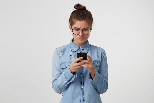 Молодая женщина с неудовольствием смотрит на смартфон в руках, надувает губы, разочарована