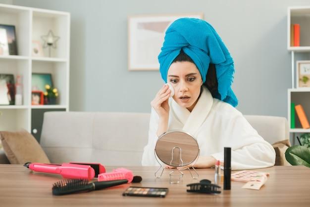 リビングルームで化粧道具とテーブルに座っているタオルでスポンジで包まれた髪とトーンアップクリームを適用して鏡を見ている若い女性