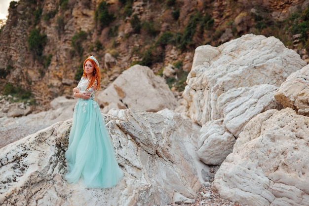 Young woman in a luxurious dress stands on the shore of the adriatic sea