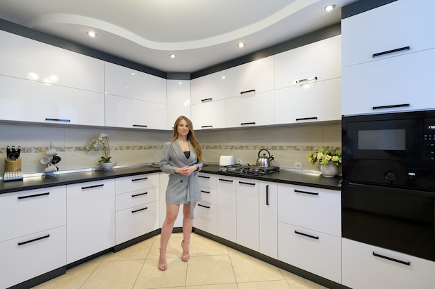 Young woman at luxury modern white kitchen interior in modern style