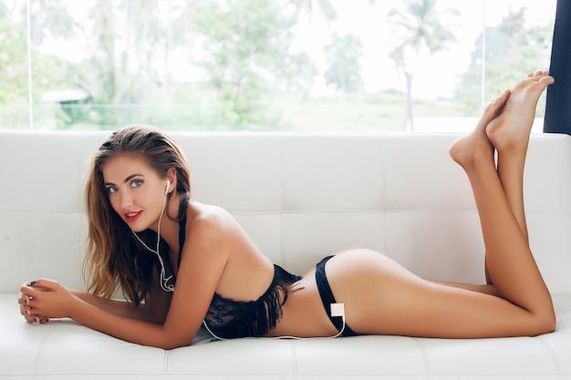 Giovane donna sdraiata da sola in lingerie nera seducente sul divano bianco in villa tropicale ascoltando musica sul lettore in auricolari sorridendo