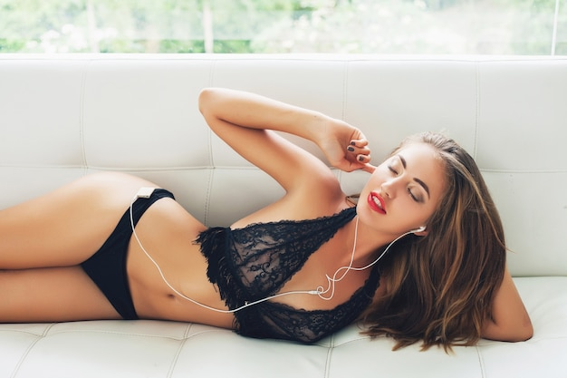 Young woman lying alone in black seductive lingerie on white sofa in tropical villa listening to music on player in earphones smiling