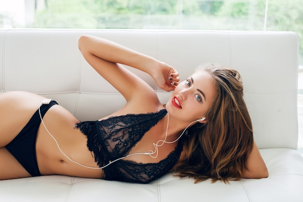 笑顔のイヤホンでプレーヤーの音楽を聴いている熱帯の別荘の白いソファに黒い魅惑的なランジェリーで一人で横たわっている若い女性