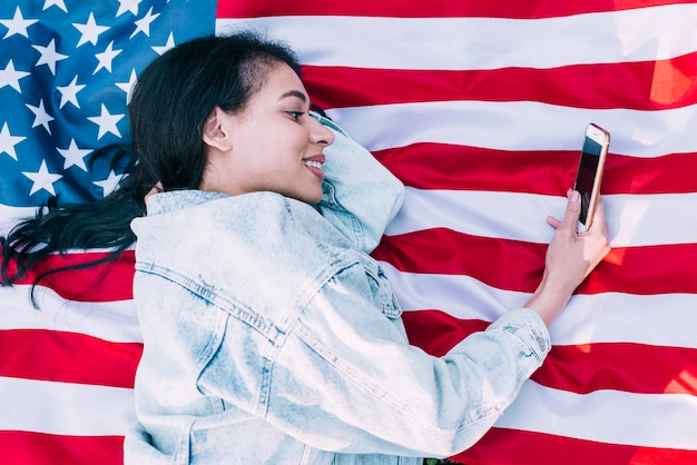 Young woman lying on american flag and using smartphone