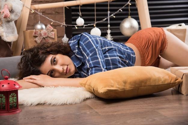 Молодая женщина, лежа и позирует с подушкой
