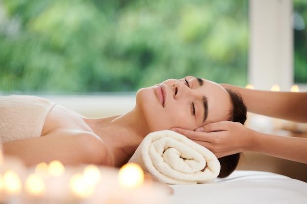 스파 마사지를 받는 동안 누워서 휴식을 취하는 젊은 여성