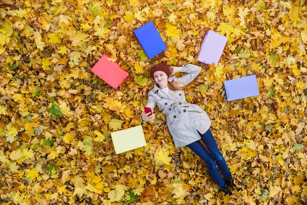 Young woman lying on autumn leaves and makes selfie surrounded by shopping bags