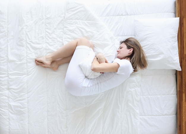 Young woman lying in bed and holding on to sore stomach top view. painful menstruation concept