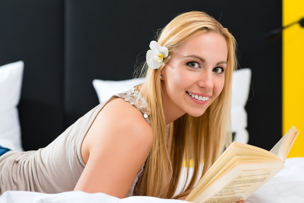 Young woman lying in the bed of a hotel room reading a book,
