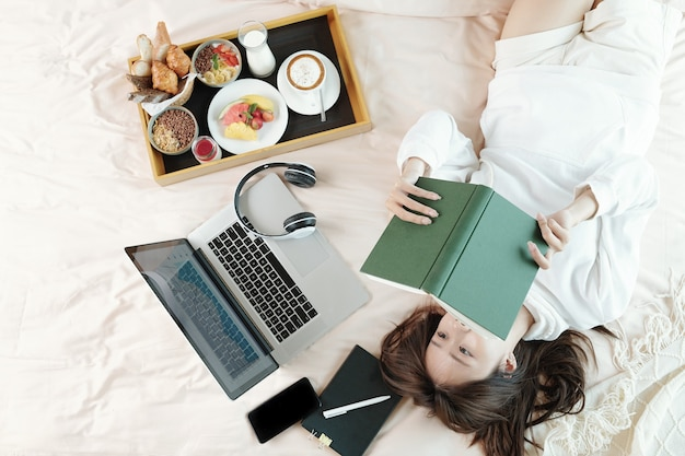 Young woman lying on bed next to laptop and tray with breakfast and reading interesting book, view from the top