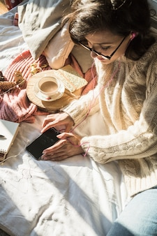 Young woman lying on bed with mobile phone and coffee