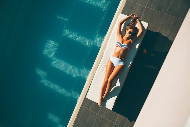 Young woman lying by swimming pool  at hot summer day
