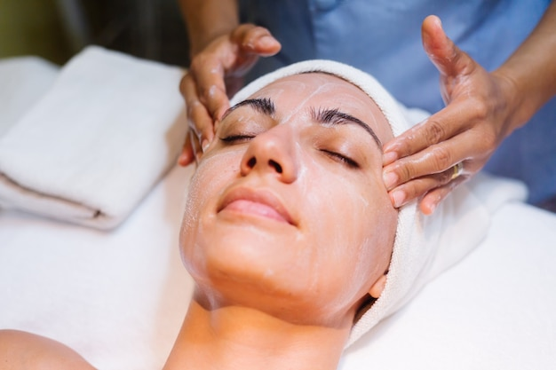 Young woman lying on cosmetologist's table during rejuvenation procedure.