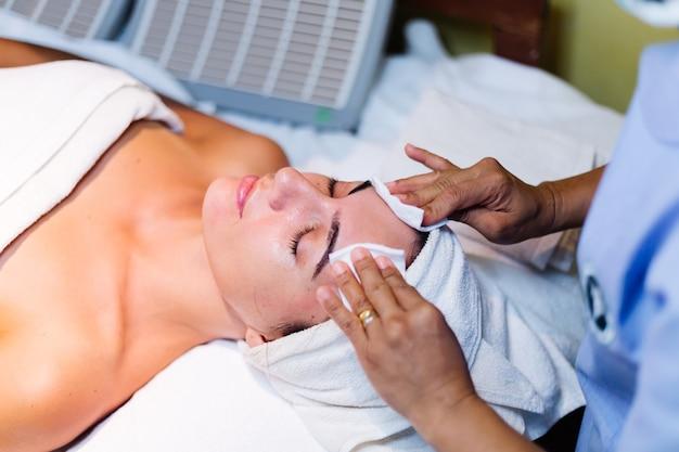 Giovane donna sdraiata sul tavolo del cosmetologo durante la procedura di ringiovanimento