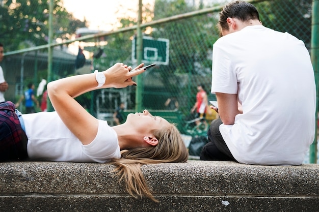 Молодая женщина, лежа в парке с помощью смартфона