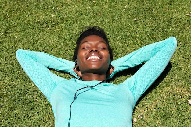 イヤホンで音楽を聴く草の上に横たわっている若い女性