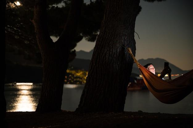 해먹에 누워 있는 젊은 여성은 달빛이 물에 반사되는 저녁 바다 옆에서 휴대전화를 검색합니다.
