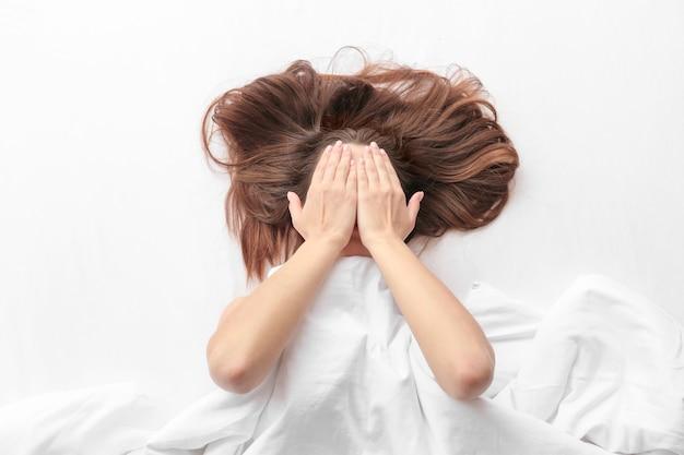 ベッドに横たわって、手で顔を覆う若い女性