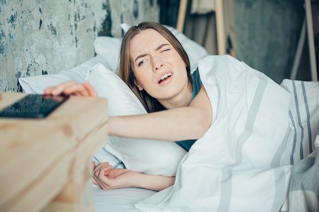 아침에 울리는 전화를 받기 위해 침대에 누워 한쪽 눈을 뜨고 있는 젊은 여성
