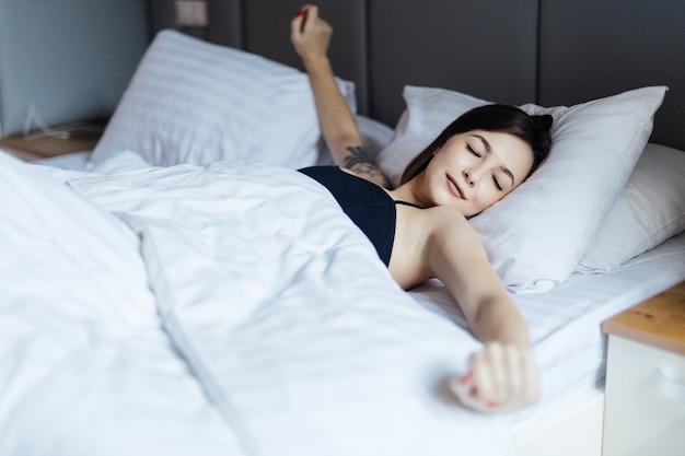젊은여자가 침대에 누워 그녀의 팔을 스트레칭