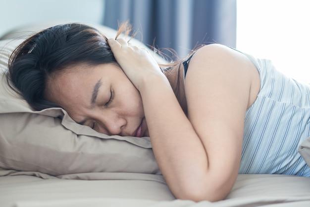 枕で頭と耳を覆う音に苦しんでベッドに横たわっている若い女性