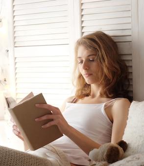 Молодая женщина, лежа в постели, читая книгу - хорошее время дома