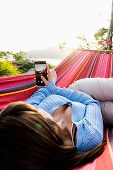 그녀의 모빌과 함께 일몰 사진을 찍고 해먹에 누워있는 젊은 여자