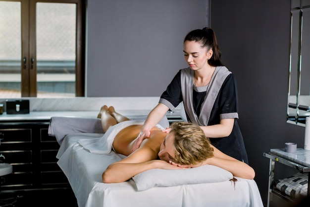 Young woman lying on a massage table, relaxing, getting professional manual back massage. young woman masseur doing massage on woman back in medical center