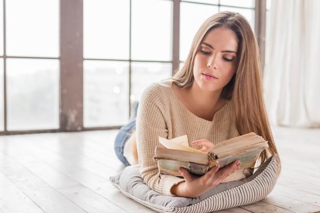 本を読んで窓の近くに横たわって若い女性