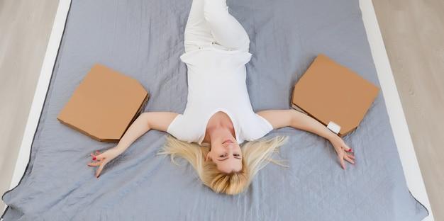 Молодая женщина, лежа на диване и ест пиццу