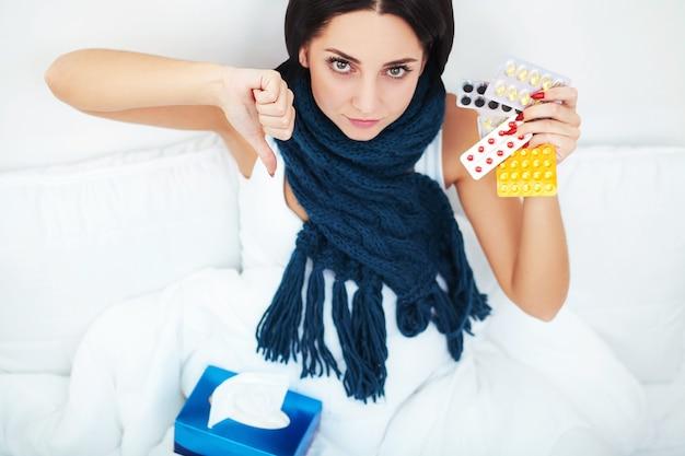 ベッドの上に横たわると薬ブリスター錠剤を保持している若い女性