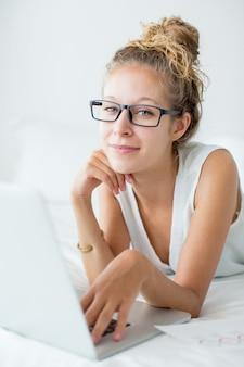 Молодая женщина, лежащая на кровати и работающая на ноутбуке
