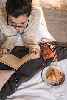 Young woman lying on blanket and reading book