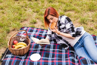 Young woman lying on blanket eating puff pastry reading book