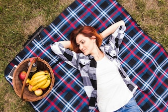 Young woman lying on blanket looking at basket with fruits and bottle